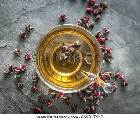 Healthy aromatic tea with dogroses buds, some buds scattered on the table, freshly brewed, topvivew #666817660