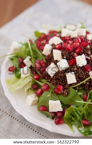 Healthy arugula salad with quinoa, feta cheese and pomegranate seeds