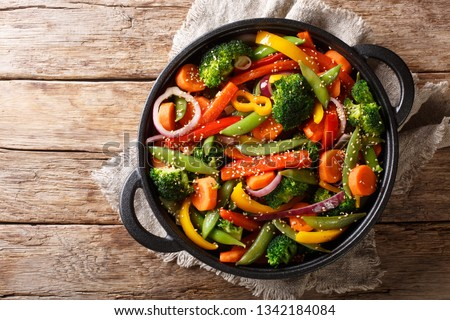Healthy Asian food stir fry of vegetables with sesame close-up in a bowl on the table, horizontal top view from above