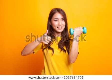 Healthy Asian woman thumbs up with dumbbells in yellow dess on yellow background - Shutterstock ID 1037654701