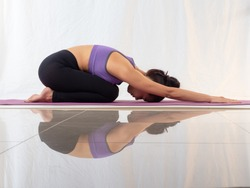 Healthy Asian woman wearing sportswear practicing yoga, Child's pose on white background wiht reflection on the floor.