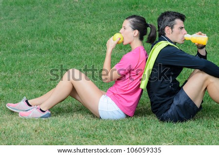 Healthy Athletes couple eating and drinking outdoor. Sporty couple taking a training break.