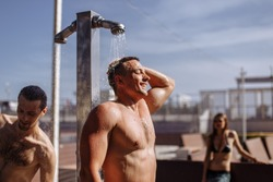 Healthy athletic young half-naked male taking outdoor shower after swimming, refreshing himself before playing beach volleyball with his friends.