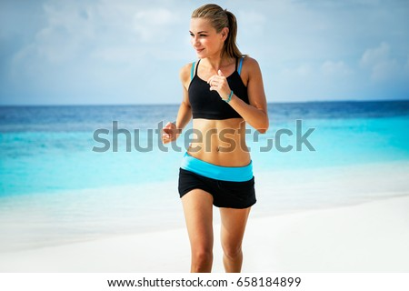 Healthy attractive woman jogging on the beautiful sandy beach, doing fitness exercise outdoors, enjoying workout near the sea, happy summer vacation