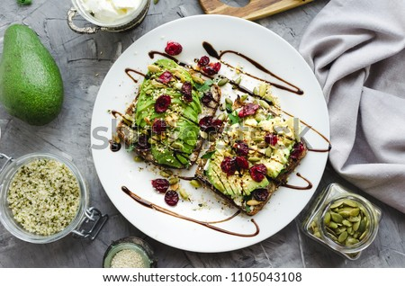 Healthy avocado toasts for breakfast or lunch with rye bread, cream cheese, arugula, sliced avocado, dried cranberry, pumpkin, hemp and sesame seeds. Vegetarian sandwiches. Clean eating. Top view.