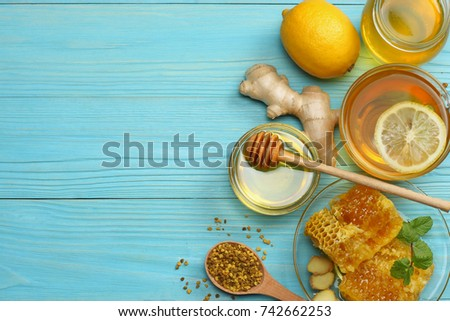 healthy background. honey, honeycomb, lemon, tea, ginger on blue wooden table. Top view with copy space #742662253