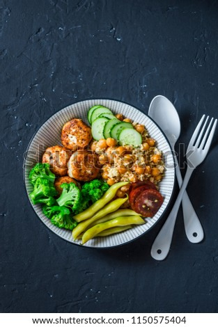 Healthy balanced buddha bowl - spicy couscous with chickpeas, broccoli, green beans and turkey meatballs on dark background, top view. Copy space