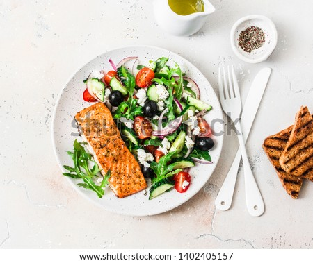 Healthy balanced lunch - grilled red fish fillet salmon and tomatoes, cucumbers, olives, feta Greek salad on a light background, top view
