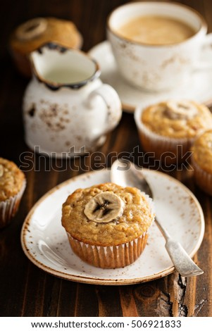 Healthy banana muffins with slices on top with coffee in dark rustic setting #506921833