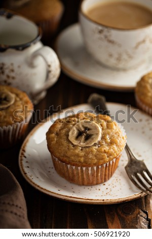 Healthy banana muffins with slices on top with coffee in dark rustic setting #506921920
