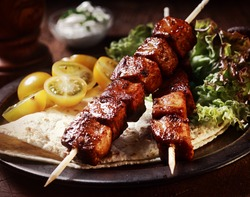 Healthy barbecued lean cubed pork kebabs served with a corn tortilla and fresh lettuce and tomato salad, close up view on a dark background