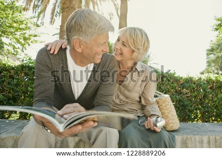 Healthy beautiful senior tourist couple relaxing in sunny park reading travel guide book, smiling outdoors. Mature man and woman on vacation trip, active leisure recreation lifestyle.