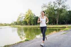 Healthy beautiful young Asian runner woman in sports clothing running and jogging on sidewalk near lake at park in the morning. Lifestyle fitness and active women exercise in urban city concept.