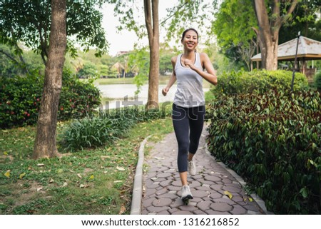 605d8c2efb2cf Healthy beautiful young Asian runner woman in sports clothing running and  jogging on sidewalk near lake