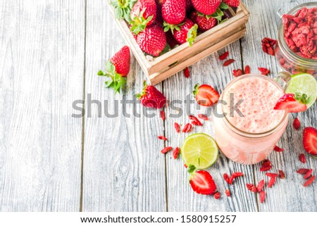 Healthy blended drink. Organic diet smoothie with lime, strawberry and goji berries, wooden background copy space #1580915257