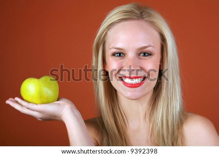 Healthy Blond girl holding a heart shaped green apple in her hand