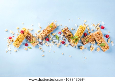 Healthy breakfast and snack concept, homemade granola with fresh raspberries and nuts and granola bars, on bright blue background copy space seamless pattern top view
