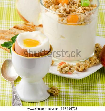 Healthy breakfast - boiled egg , yogurt with muesli