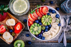 Healthy breakfast bowl: oatmeal with banana, kiwi, strawberry, blueberries and chia seeds