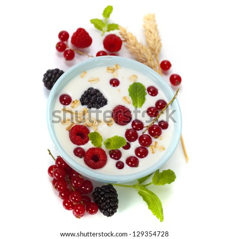 healthy breakfast: bowl of cerial with yogurt or milk, fresh berries and mint over white - stock photo