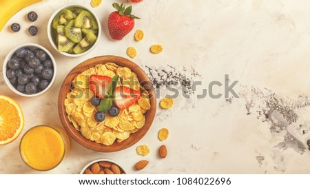 Healthy breakfast - bowl of corn flakes, berries and fruit, nuts, orange juice, milk, top view. #1084022696