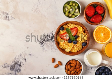 Healthy breakfast - bowl of corn flakes, berries and fruit, nuts, orange juice, milk, top view. #1157930968