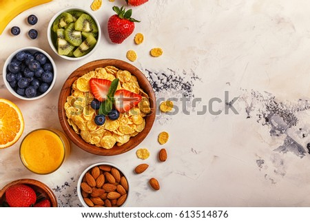 Healthy breakfast - bowl of corn flakes, berries and fruit, nuts, orange juice, milk, top view. #613514876
