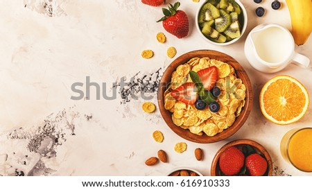 Healthy breakfast - bowl of corn flakes, berries and fruit, nuts, orange juice, milk, top view. #616910333