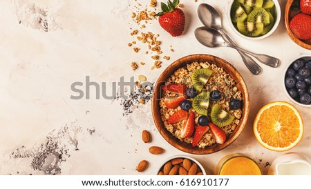 Healthy breakfast - bowl of muesli, berries and fruit, nuts, orange juice, milk, top view. #616910177