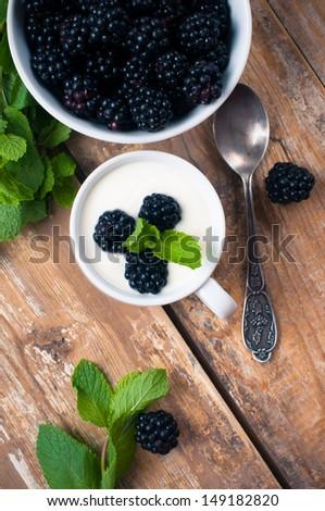 Healthy breakfast, creamy yogurt with blackberries, fruit cream dessert in a cup, on a wooden board in a rustic vintage style.