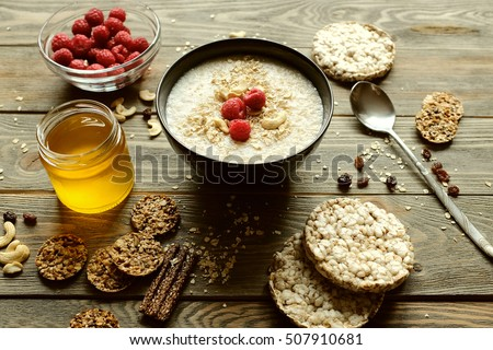 Healthy breakfast. Crispbread, raspberries and honey on the table, wooden background #507910681