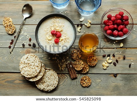 Healthy breakfast. Crispbread, raspberries and honey on the table, wooden background #545825098