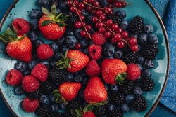 Healthy breakfast eating a mix of raw fresh berries fruits
