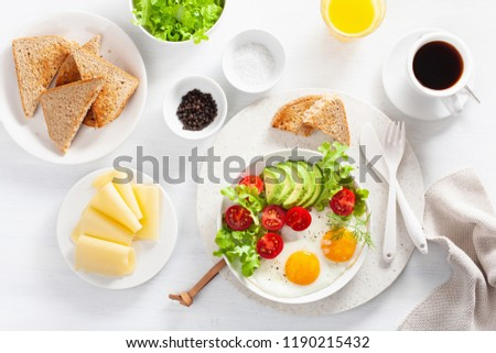 healthy breakfast flat lay. fried eggs, avocado, tomato, toasts and coffee