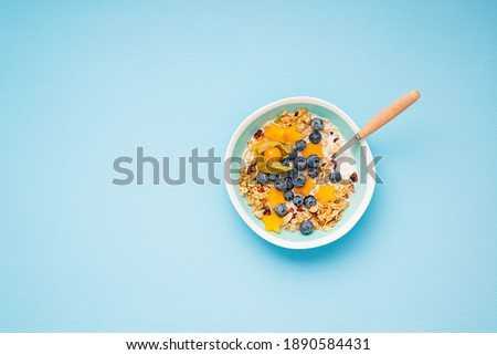 Healthy breakfast. Fresh granola, muesli with milk, honey and berries. Blue color background.Top view Foto stock ©