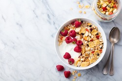 Healthy breakfast. Fresh granola, muesli with yogurt and berries on marble background. Top view. Copy space.