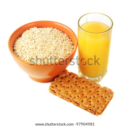 Healthy breakfast: fruit juice, crisps and oat grains in ceramic bowl - stock photo