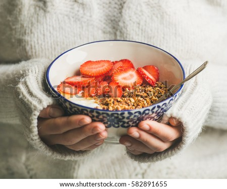 Healthy breakfast greek yogurt, granola and strawberry bowl in hands of woman wearing white loose woolen sweater, selective focus. Clean eating, healthy, vegetarian, dieting food concept #582891655