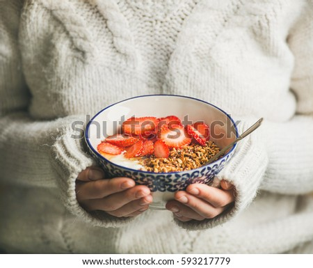 Healthy breakfast greek yogurt, granola and strawberry bowl in hands of woman wearing white loose woolen sweater, selective focus. Clean eating, healthy, vegetarian, dieting food concept #593217779