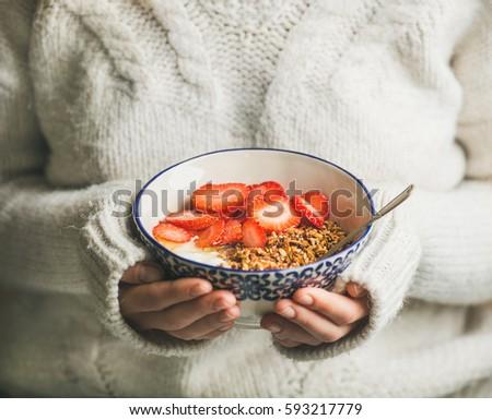 Healthy breakfast greek yogurt, granola and strawberry bowl in hands of woman wearing white loose woolen sweater, selective focus. Clean eating, healthy, vegetarian, dieting food concept #593217779