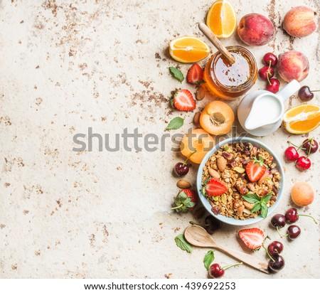 Healthy breakfast ingredients. Bowl of oat granola with milk, fresh fruit, berries and honey. Top view, copy space