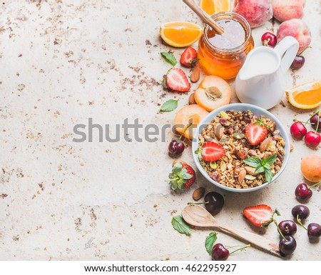 Healthy breakfast ingredients. Oat granola in bowl with nuts, strawberry and mint leaves, milk in pitcher, honey in glass jar, fresh fruits and berries on light concrete background, top view #462295927