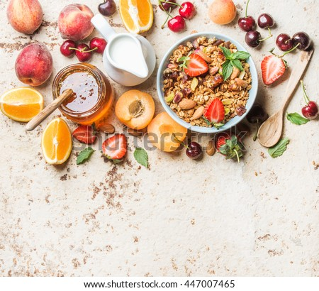 Healthy breakfast ingredients. Oat granola in bowl with nuts, strawberry and mint, milk, honey, fruit and berries on light concrete background, top view, copy space, horizontal composition #447007465