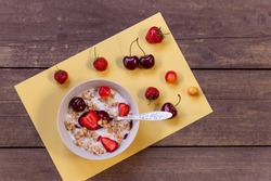Healthy breakfast.muesli with milk and berries - health and diet concept.vegetarian breakfast. Oatmeal, granola with strawberries and cherry in bowl over woodenbackground.Copy space