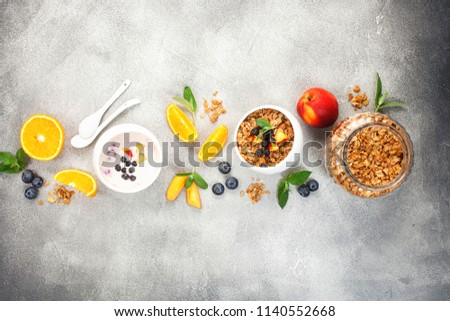 Healthy breakfast - muesli, yogurt with fruits and berries on s grey background.  Copy space. Top view #1140552668