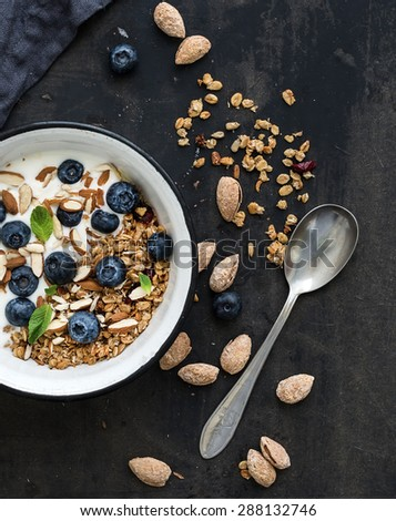 Healthy breakfast. Oat granola with fresh blueberries, almond, yogurt and mint in a rustic metal bowl over dark grunge surface. Top view