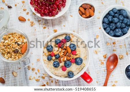 Healthy breakfast: oatmeal porridge with fresh blueberries, raspberries and muesli. Overhead view