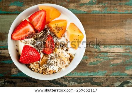 Healthy breakfast of muesli, strawberries and melon with kefir yogurt and chia seeds.