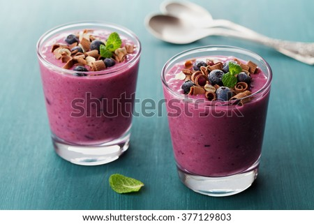 Healthy breakfast of smoothie, dessert, yogurt or milkshake with frozen blueberry and oats decorated grated chocolate and mint leaves on wooden rustic table
