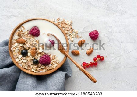 Healthy breakfast on concrete background. Bowl of muesli with natural yogurt, almonds and fresh raspberries. Top view.